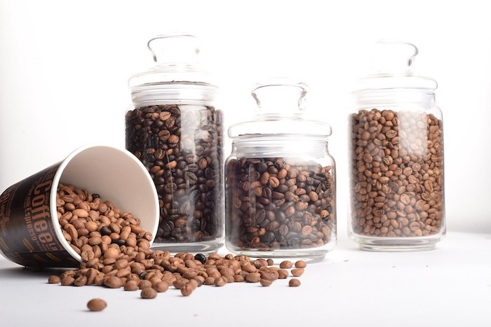 varying sizes of glass jars half-filled with whole coffee beans