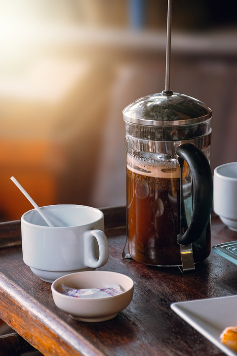 French press coffee at center of a wooden block