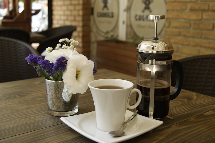 A cup of coffee on a table, with a french press.