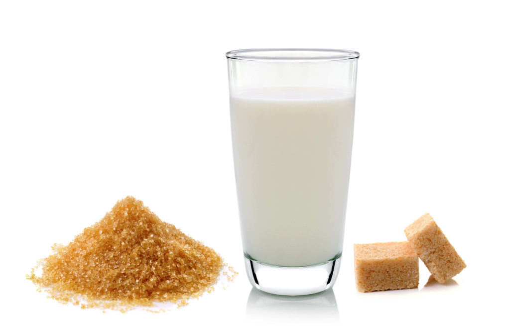 a glass of milk and cubes of sugars beside it