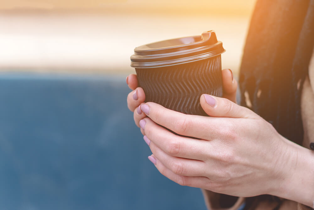 Female hand holding a black coffee cup