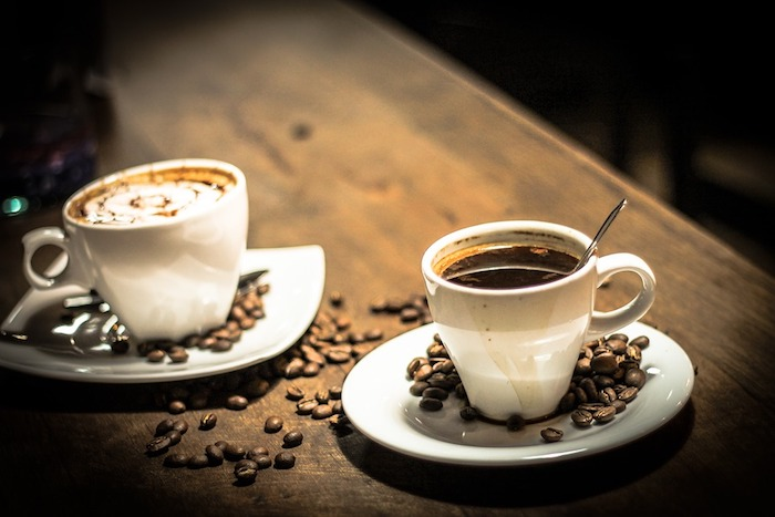 A cup of coffee on a table, with Espresso and Coffee bean