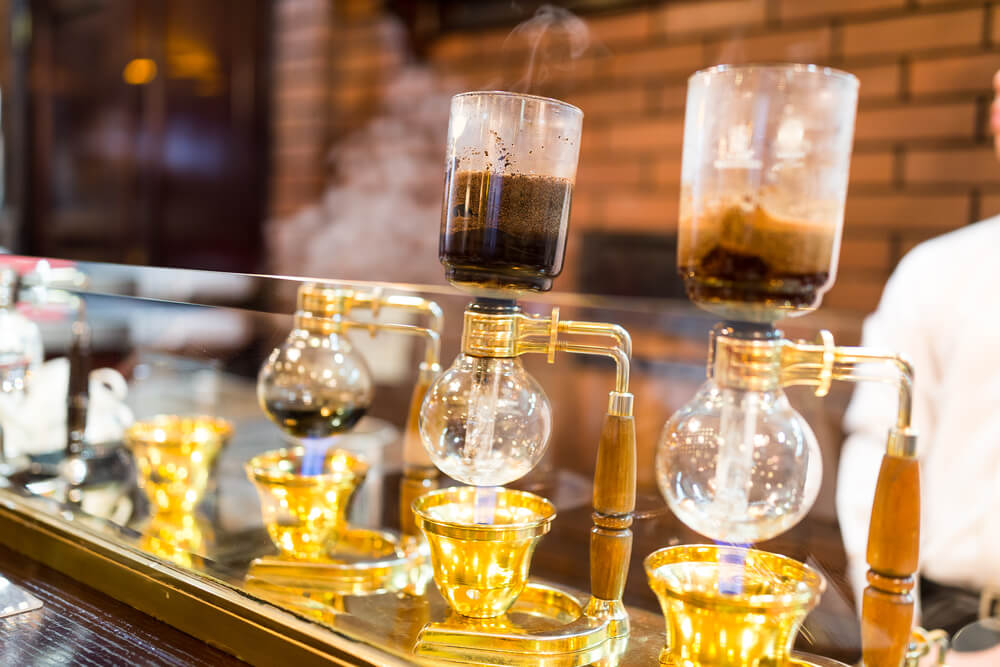siphon coffee brewer at a coffee bar - how to brew coffee with a siphon