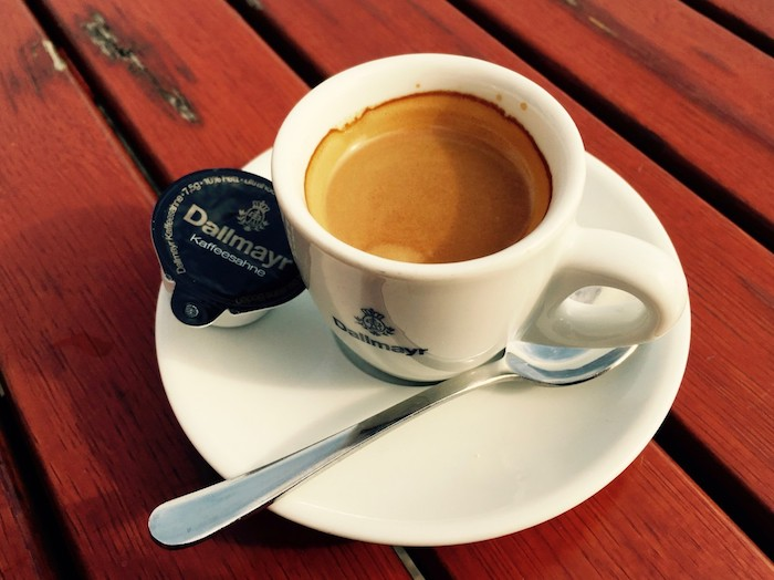 A cup of espresso coffee sitting on top of a wooden table