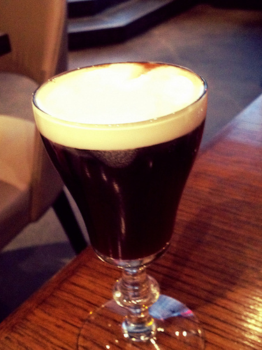 A cup of coffee on a table, with Irish coffee and Coffee bean