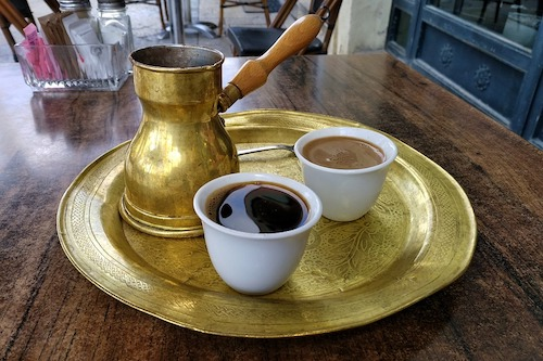 Turkish coffee on a table with a coffee pot.
