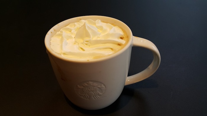 A cup of coffee on a table, with cream.