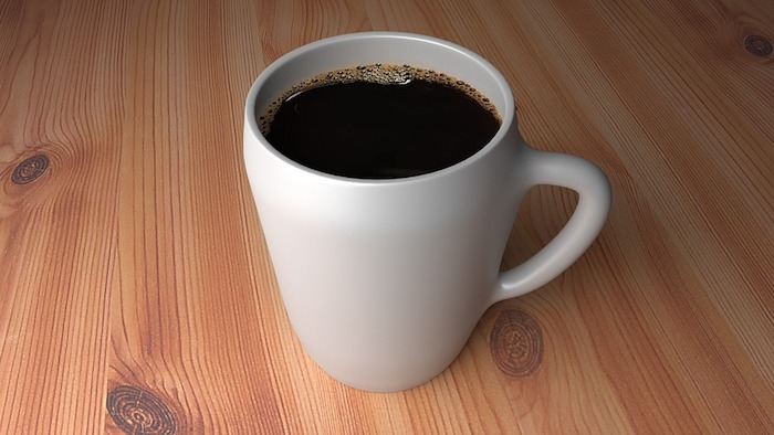 A close up of a coffee cup sitting on top of a wooden table, with Espresso and Caffeine