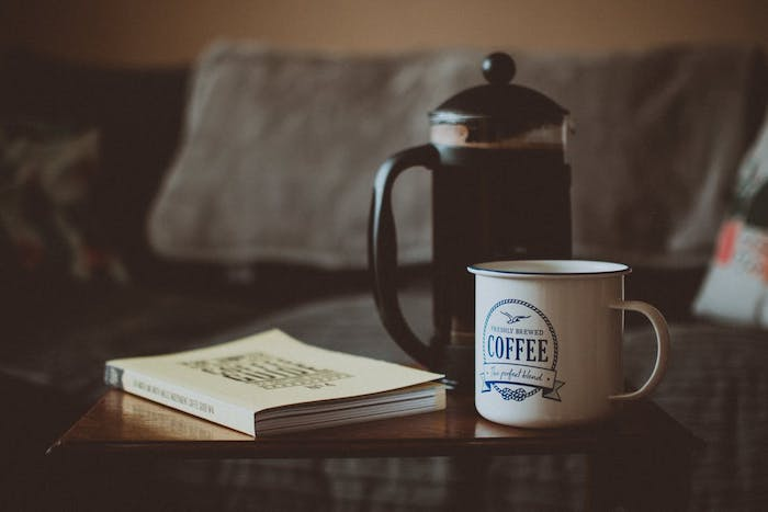 A cup of coffee on a table, with a coffee pot - can you put a french press in the fridge