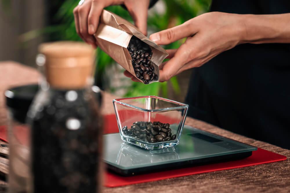 Weighing coffee grains on digital scale