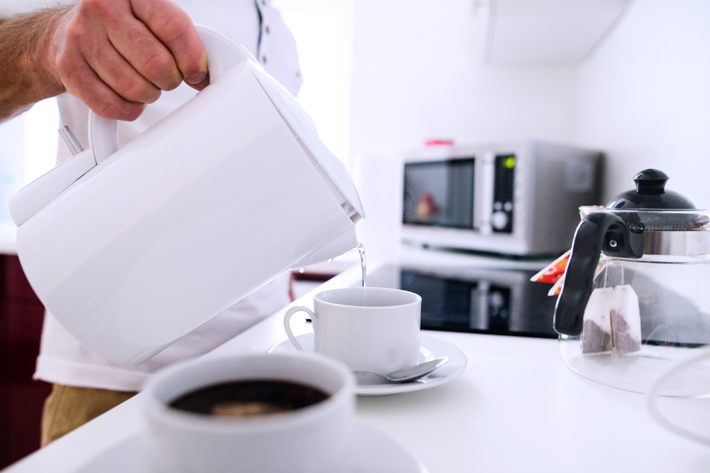 Pouring hot water from electric kettle into prepared cups.