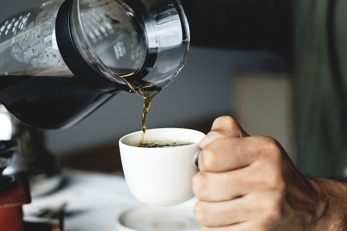 Brewed coffee being poured into a cup.