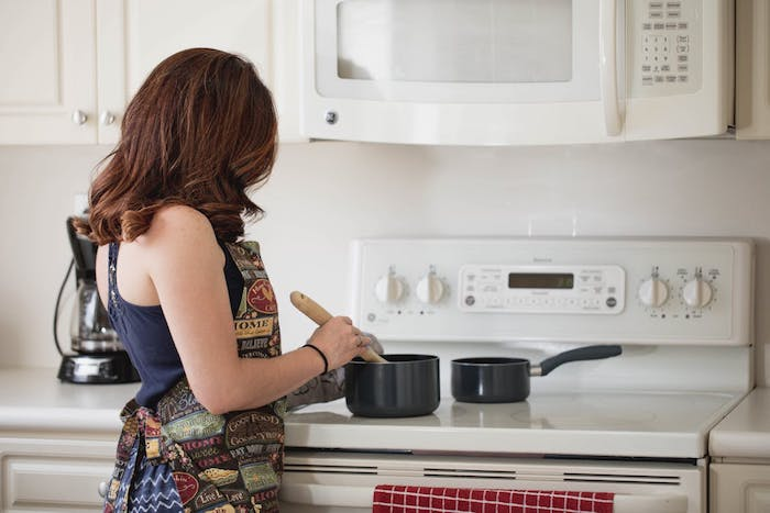 A woman standing in front of a stove top oven heating coffee in a pan.