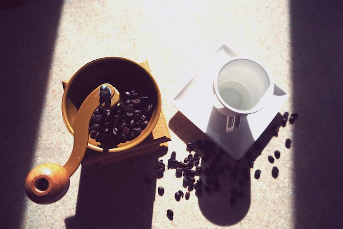A cup, with coffee grinder and coffee beans.