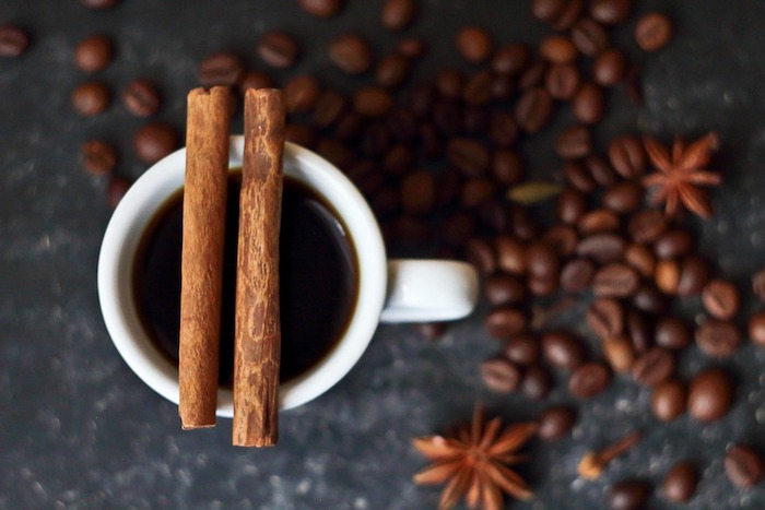A close up of a coffee cup, with Cinnamon in coffee - How To Dissolve Cinnamon In Your Coffee