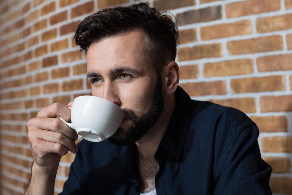 young bearded man drinking coffee
