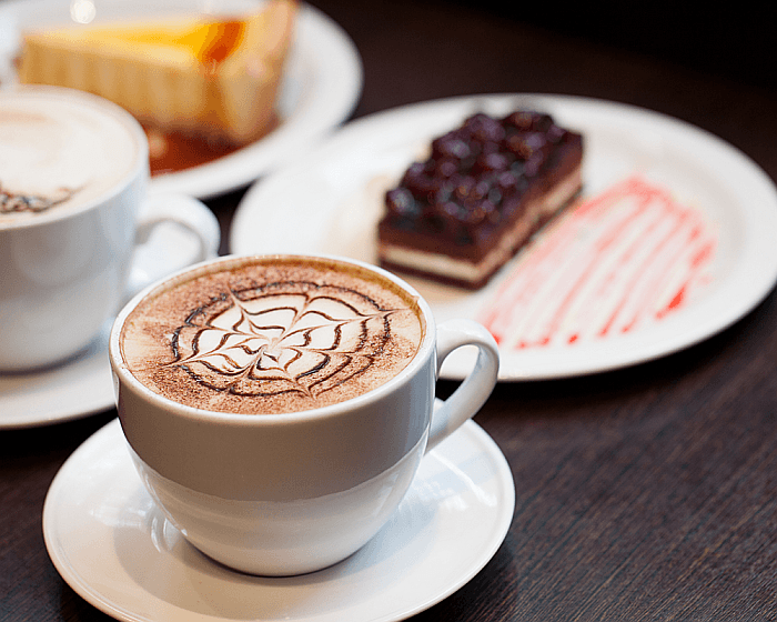 A close up of a cup of Cappuccino and a cake.