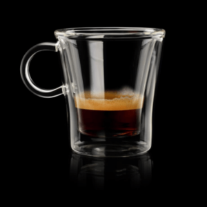 A glass cup on a table, with Espresso coffee.