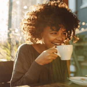 A person sitting at a table with a cup of coffee.