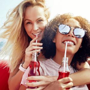 Women drinking from bottles of soda using straws.