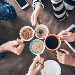 A group of people sitting at a table with a plate of food, with coffee.
