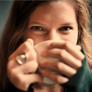A woman cupping a cup of coffee.