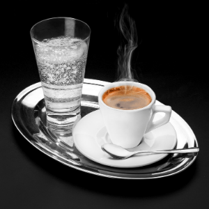A cup of coffee on a table, with a glass of soda.