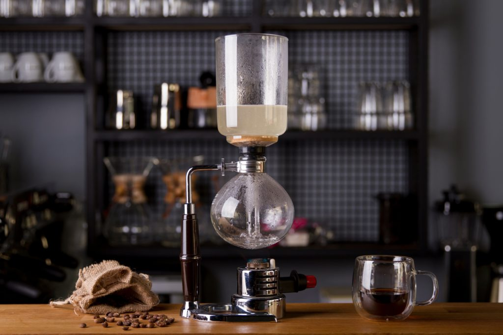 siphon coffee, a cup of coffee, and coffee beans