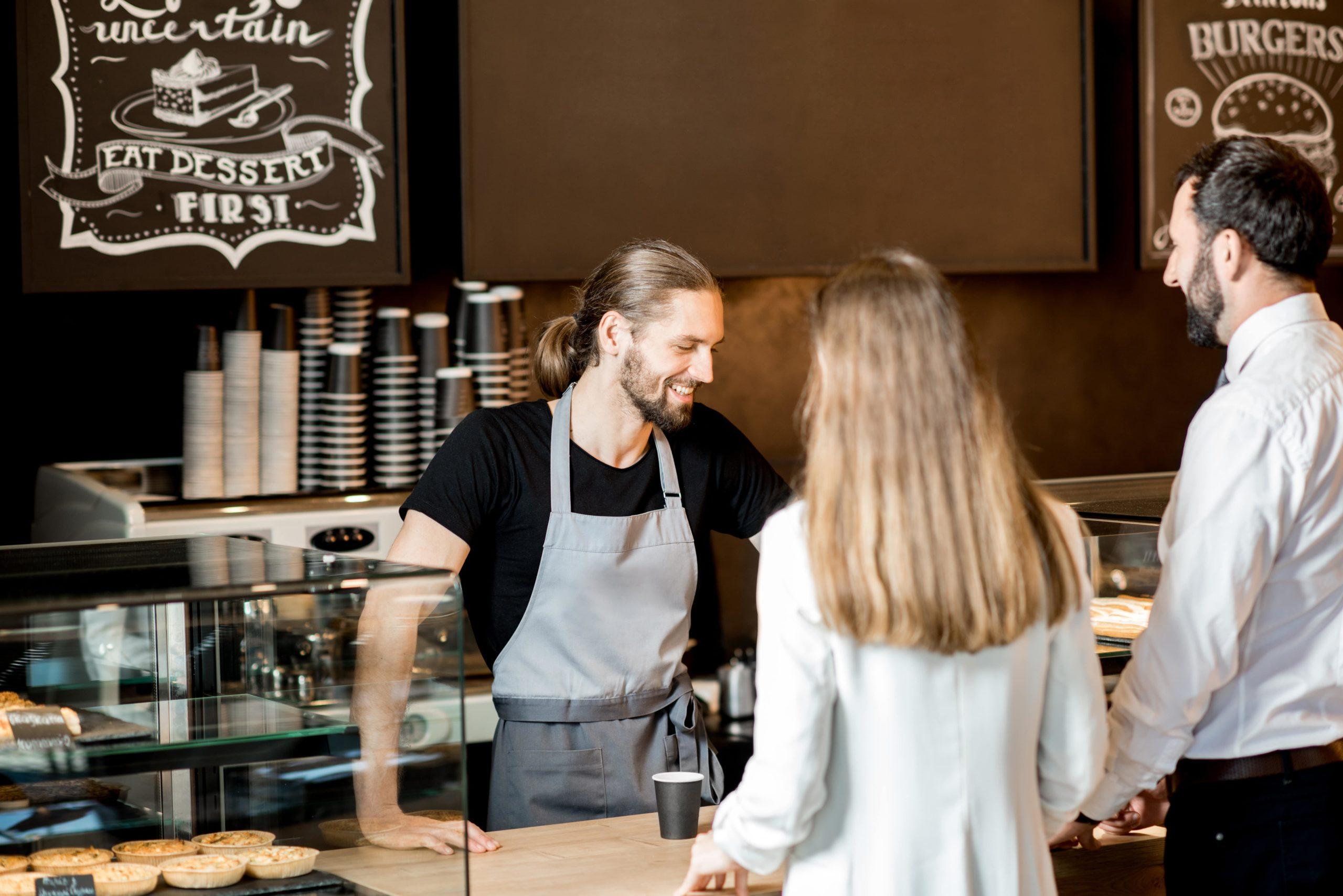 A woman buying coffee from a barista.
