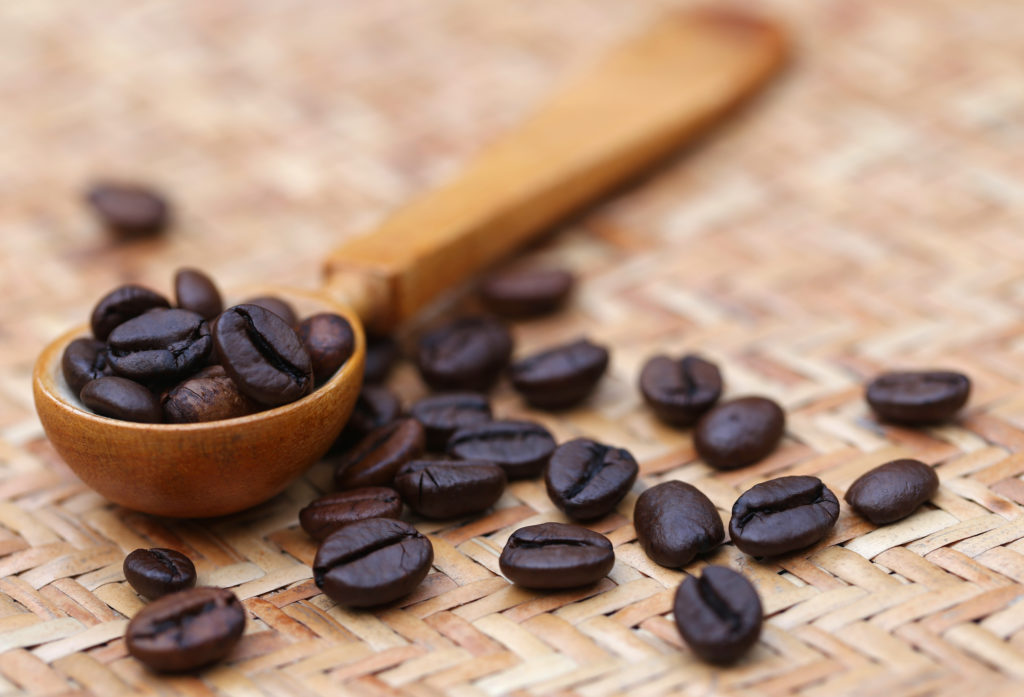 Roasted coffee beans in a spoon.