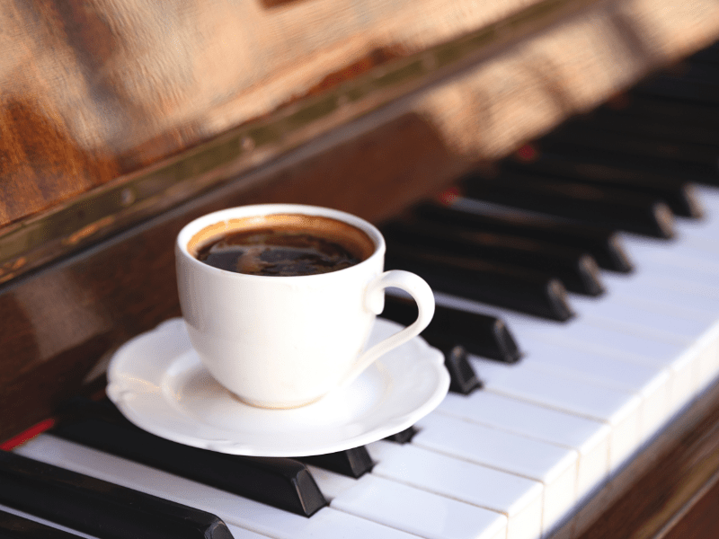 A cup of coffee on a piano.
