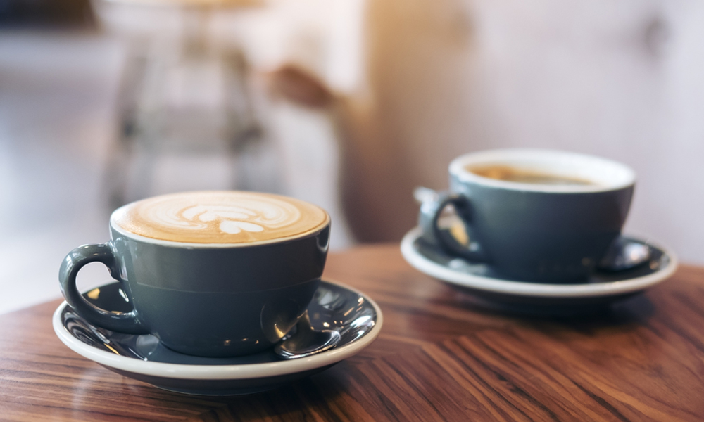 A cup of coffee on a table, with Espresso and Latte