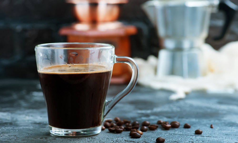 A glass of brewed coffee using freshly ground beans.
