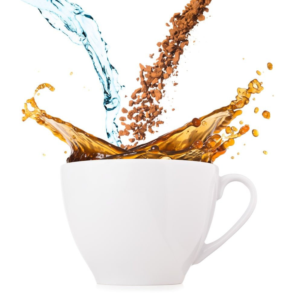Coffee in a cup showing water, brewed coffee and instant coffee granules.
