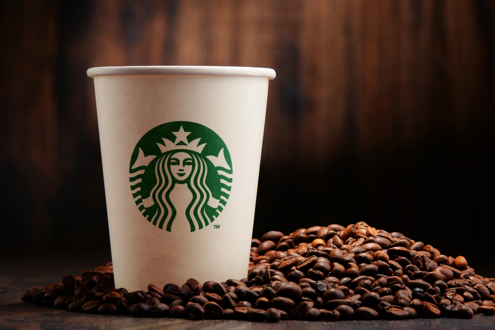 a Starbucks coffee with coffee beans beside it