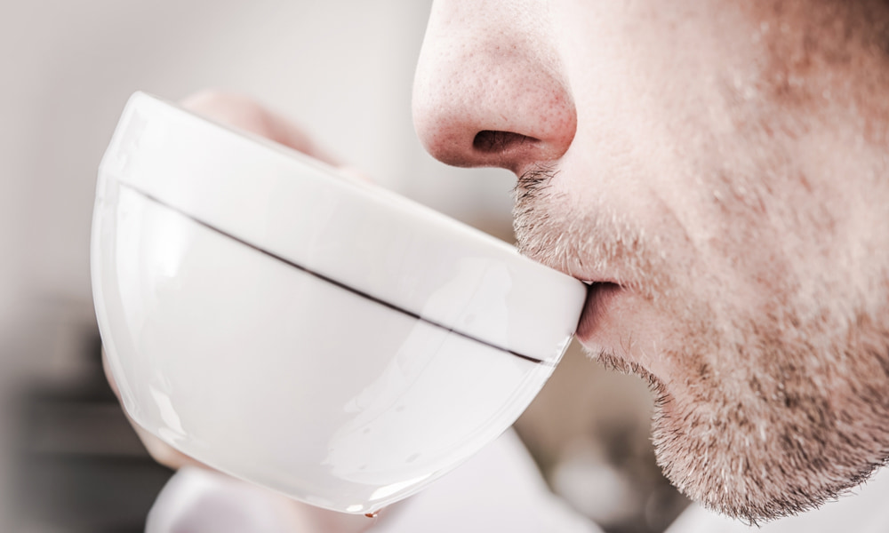 Man drinking from an espresso coffee cup.