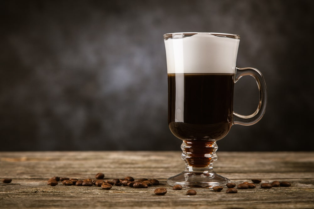 A glass mug on a table, with a cold brew coffee liqueur.