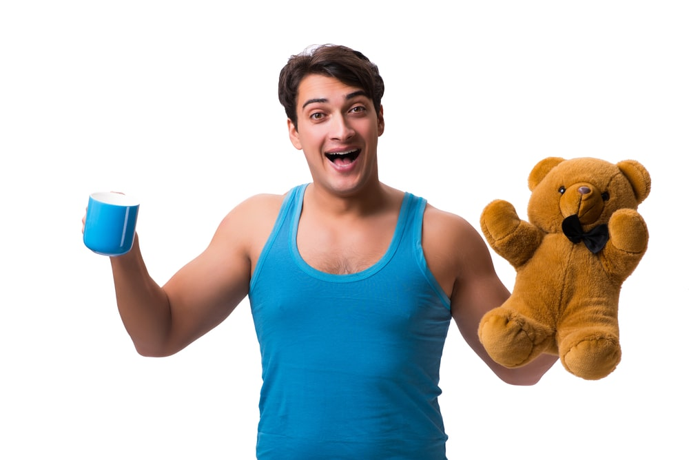 A man holding a teddy bear posing for the camera