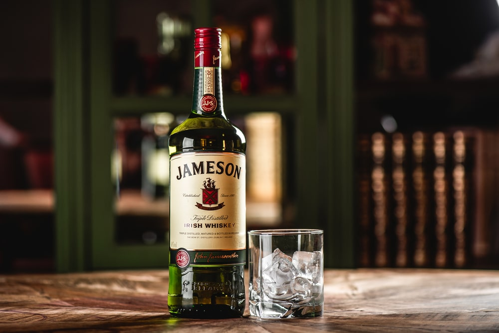 A bottle of whiskey sitting on top of a wooden table