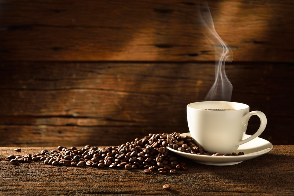 A cup of coffee sitting on top of a wooden table, with Espresso and Coffee bean