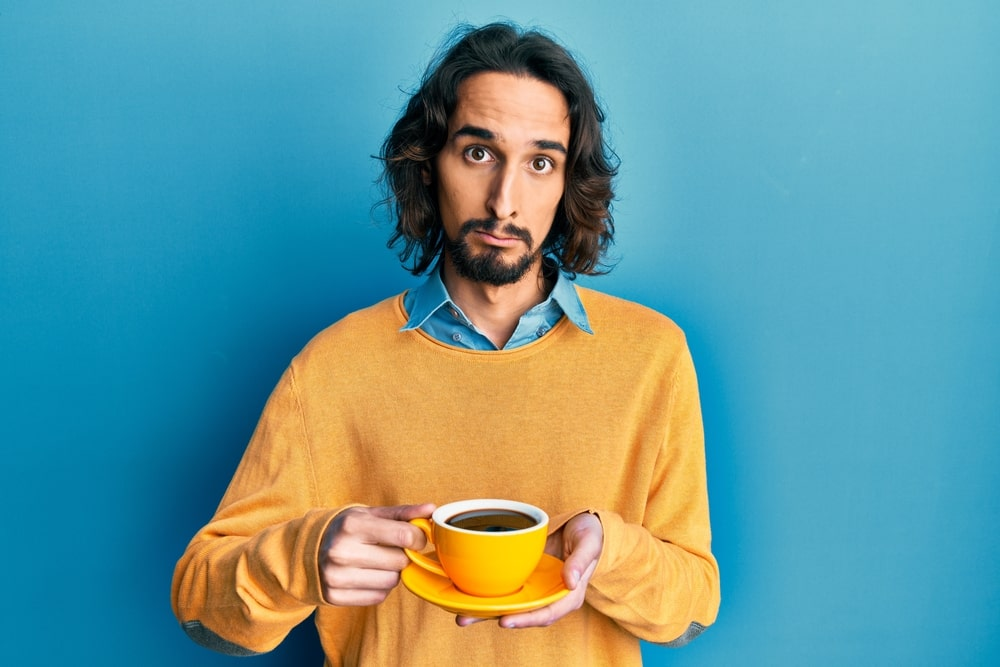 A person holding a cup, with Coffee