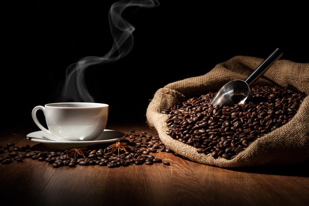 steaming coffee mug and bag of beans