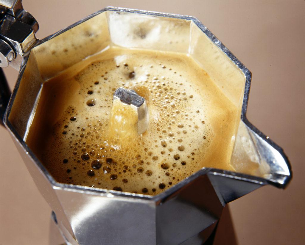 Frothy freshly percolated espresso coffee in a stovetop moka espresso pot