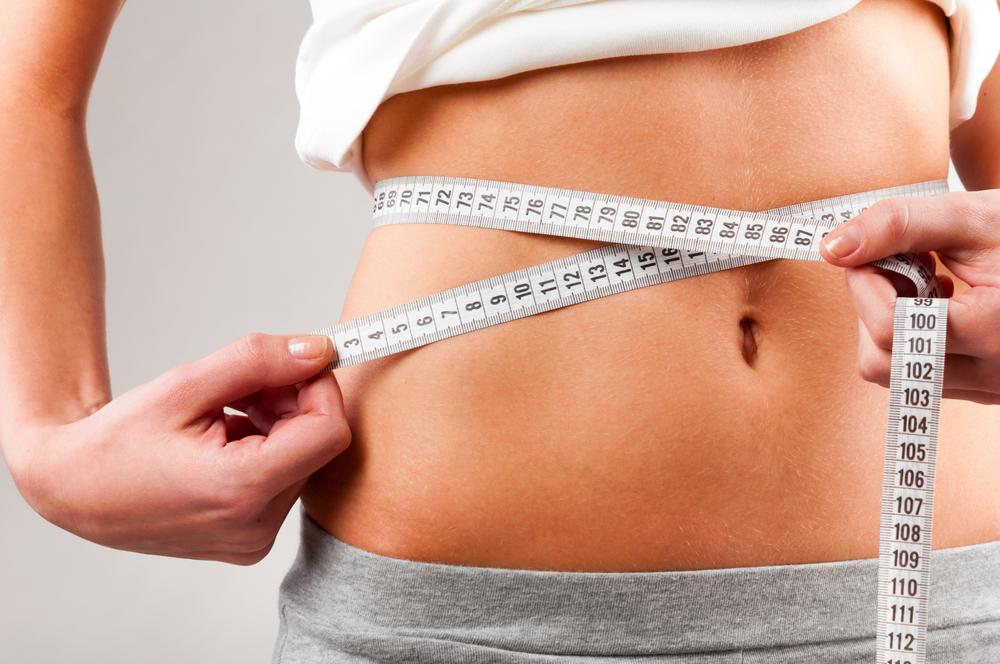 measuring waist using a white tape measure