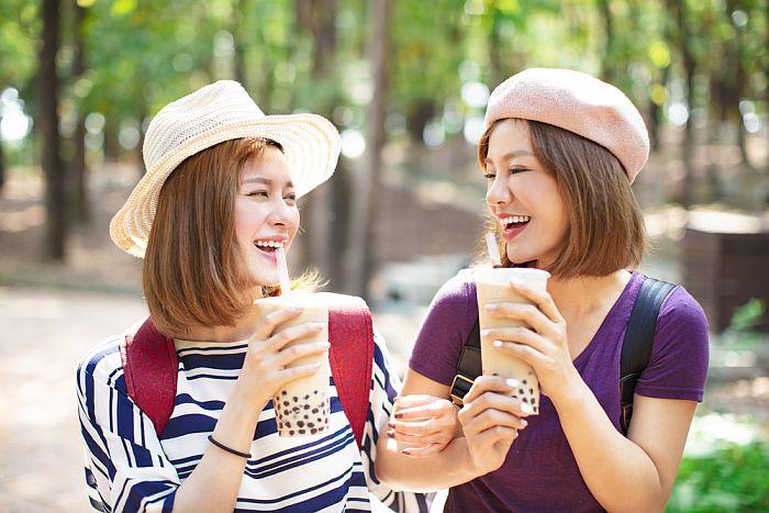 Women drinking bubble tea outside.