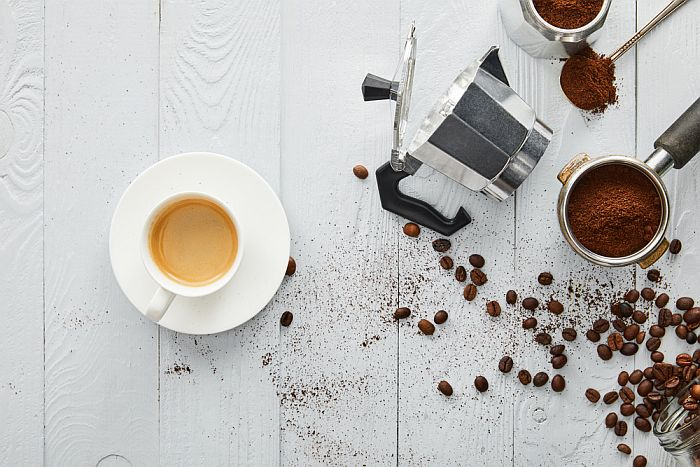 Espresso in a cup with a coffee pot and coffee beans.