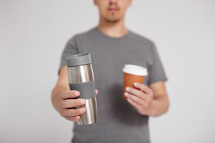 Reusable coffee cup over a disposable paper cup