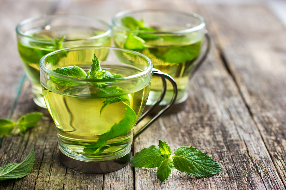 Hot mint tea in glass cup on wooden background, selective focus