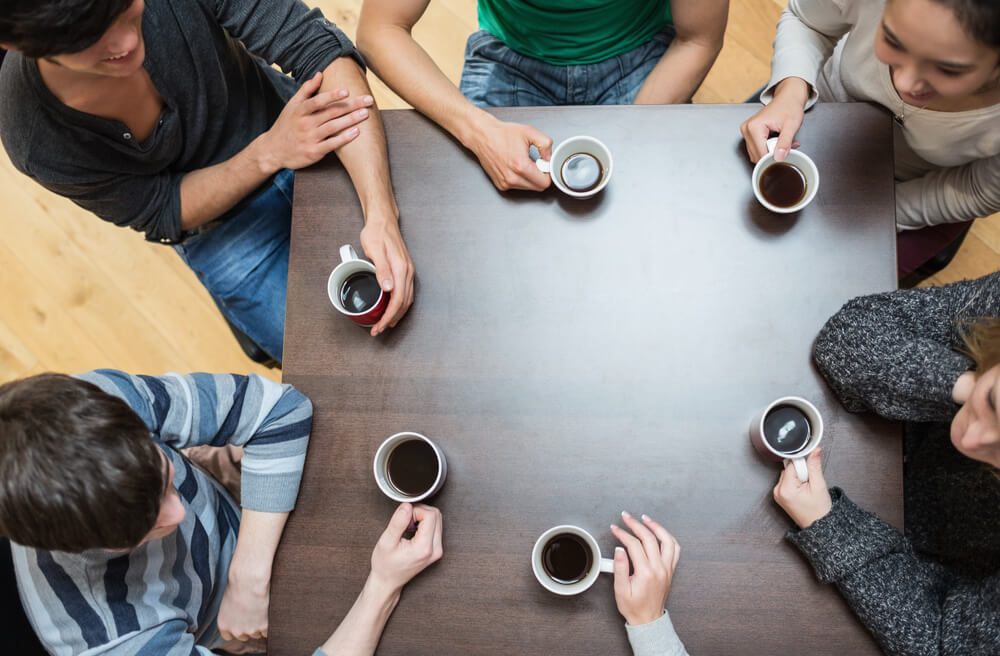 people sitting around a round table drinking coffee