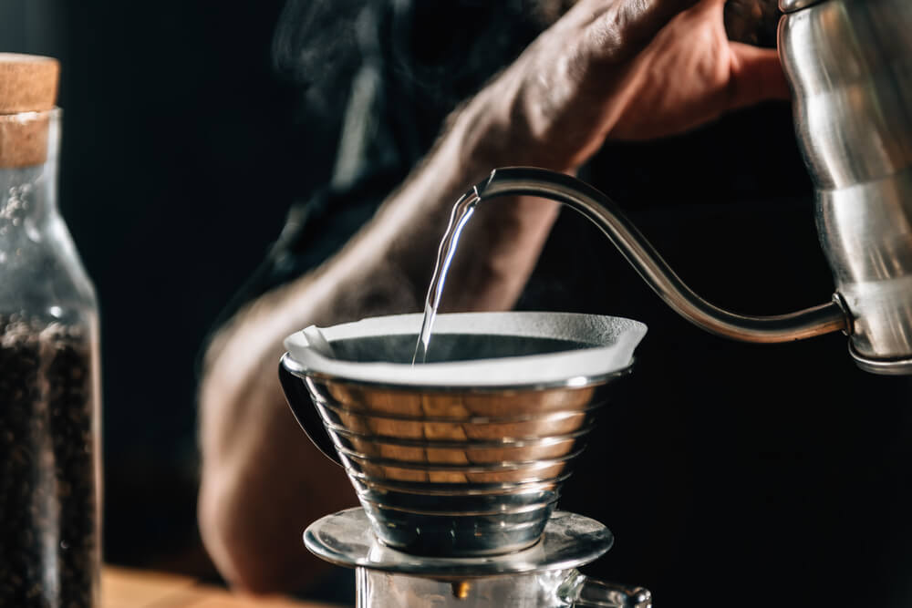pouring hot water to the ground coffee